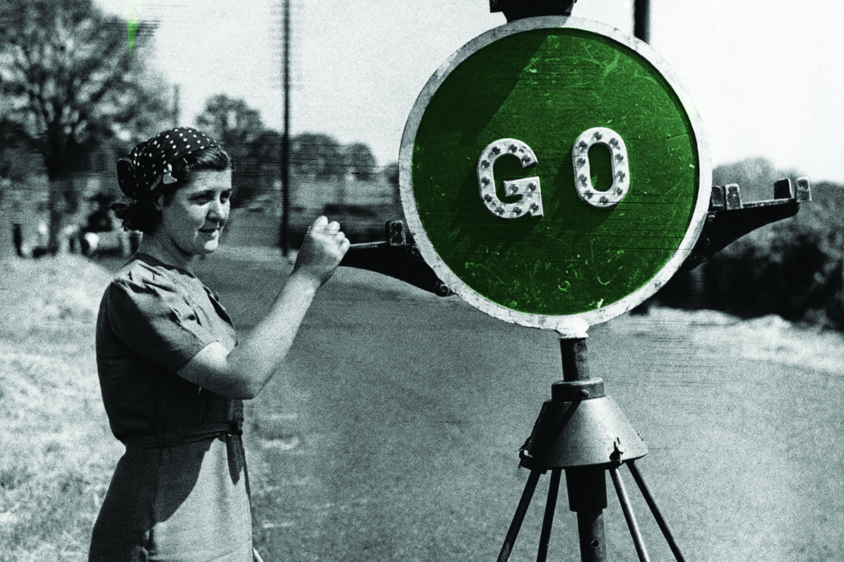 A female traffic controller employed by Shropshire County Council as part of the War effort, operates a stop and go sign on a country road, 1941. (Photo by © Hulton-Deutsch Collection/CORBIS/Corbis via Getty Images)
