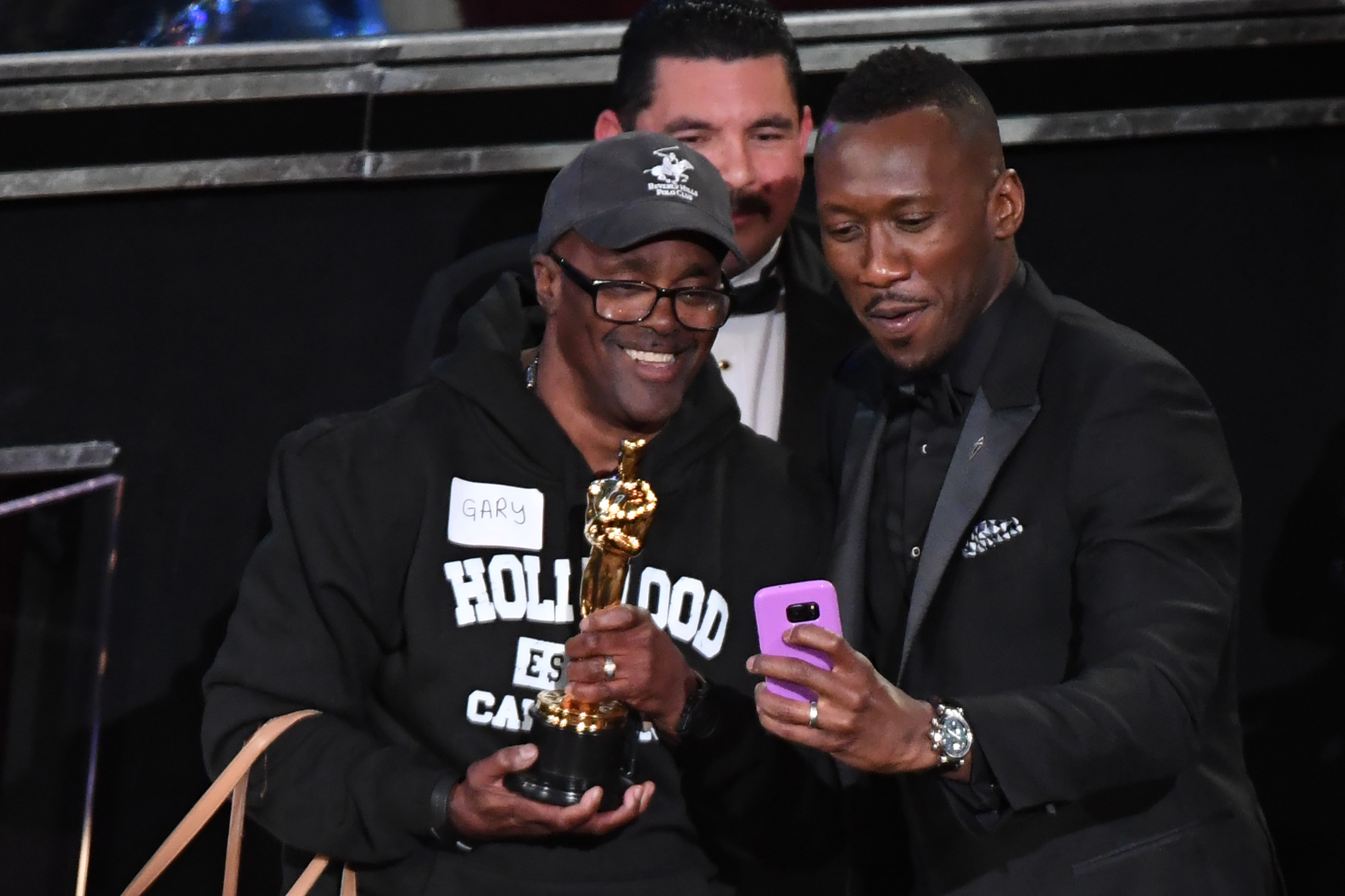 TOPSHOT - A tourist brought into the Oscars as a surprise meets with Best Supporting Actor winner Mahershala Ali at the 89th Oscars on February 26, 2017 in Hollywood, California. / AFP / Mark RALSTON (Photo credit should read MARK RALSTON/AFP/Getty Images)