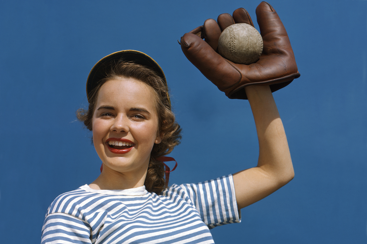 Young teen girl posed with a baseball glove in the air catching a ball, Los Angeles, California, 1950. (Photo by Camerique/Getty Images)