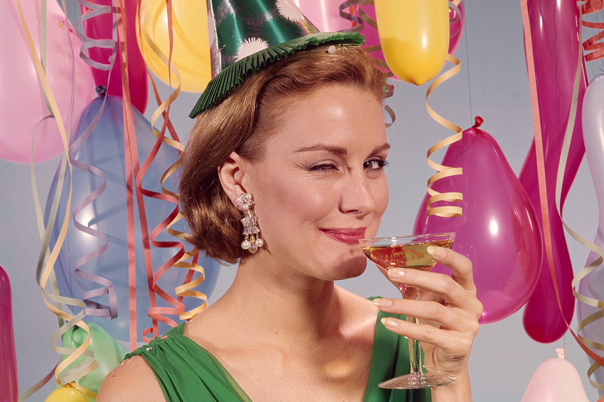 UNITED STATES - CIRCA 1960s: Woman at party, wearing party hat and winking, holding glass of wine. (Photo by H. Armstrong Roberts/Retrofile/Getty Images)