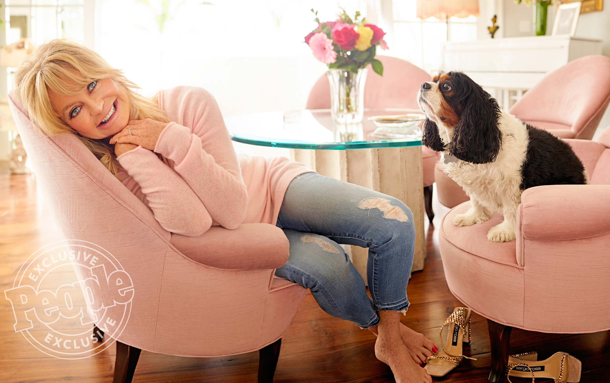 Goldie Hawn photographed with her dog, Rupert, at her house in Los Angeles, CA, on May 5, 2017. Photographer: Peggy Sirota Hair: Riawna Capri/KÈrastase Aura Botanica/Cloutier Remix Makeup: Joey Maalouf/ISH.co/TheOnly.Agency Stylist: Sophie Lopez/TheOnly.Agency Clothing Credits: Pink Sweater - White and Warren Cami ñ Dolce and Gabbana Jeans ñ Mother Denim (Goldieís own) Shoes ñ Sergio Rossi Earrings Ippolita